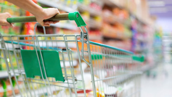 Woman pushing a shopping cart down a supermarket isle