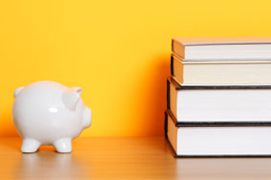 piggy bank next to a stack of textbooks
