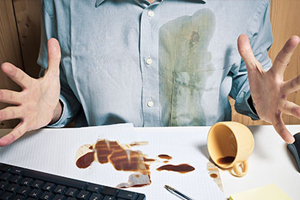 person spilled coffe on shirt and work on desk
