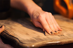 woman sanding an old wooden tabletop