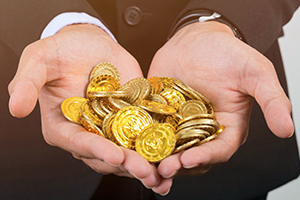 man holding gold bitcoins in his upturned palms