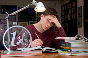 MaleStudent studying at desk, with head in hand