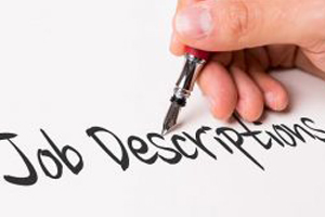 Hand using brush and ink to write job description