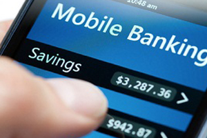 Closeup of person's thumb over mobile banking app displayed on mobile device