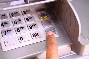 Image of a finger over the keypad of an ATM machine
