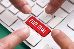 Four fingers pointing towards a free trial button on a keyboard