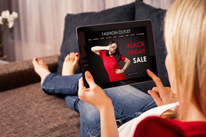 Woman at home views tablet showing black friday sale ad