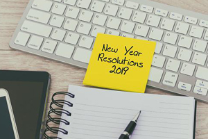 "syellow sticky note on computer keyboard next to planner that reads,"" New years' Resolutions 2019"""