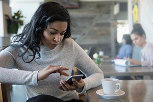 Young black woman scrolling through an app on her smartphone in a cafe