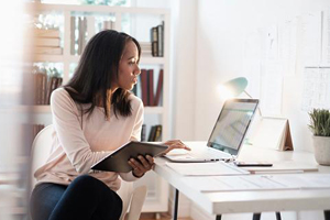 Young black woman working on her budget on a laptop