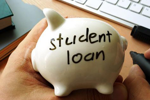 """Hand holding a small, white, porcelain piggy bank with """"student loan"""" handwritten on the side."""