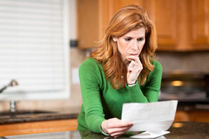 Middle-aged red-haired woman in modern studying credit report witha look of concernkitchen