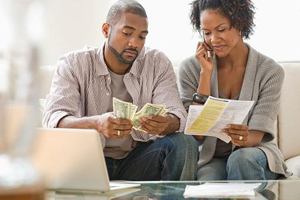 Young black couple counting money and comparing to bills due with looks of concern