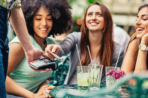 Young woman hands waiter her chip enabled card to pay for her and her friends lunch at an outdoor cafe.