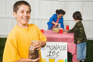 young friends run a lemonade stand. A boy in a yellow shirt holds a coin jar and smiles.